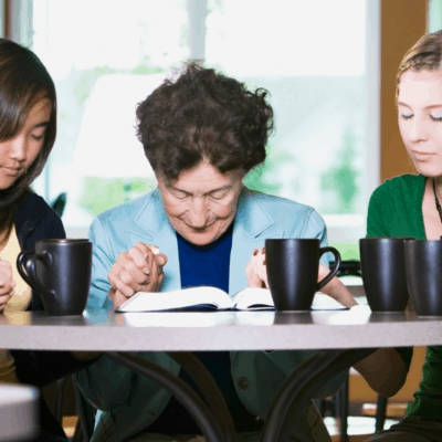 image of women around table praying