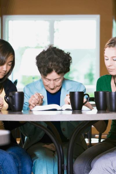 image of women around table praying
