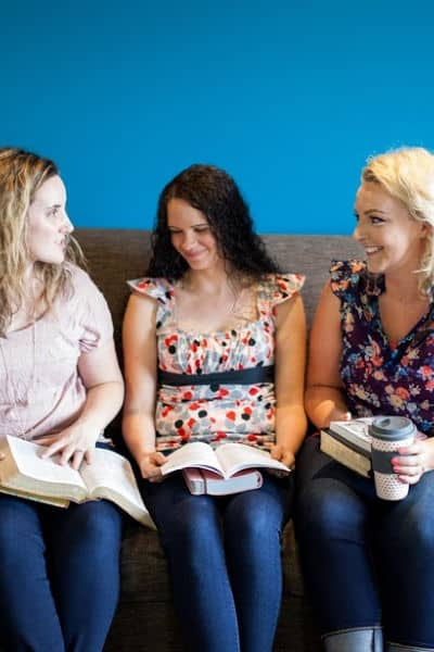 Women sitting on couch with Bibles.