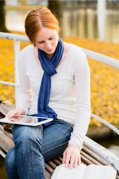 image of red haired woman sitting on bench reading Bible