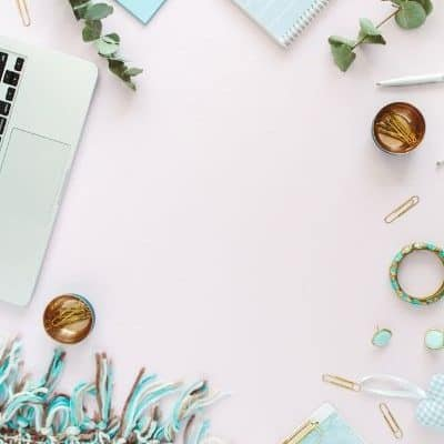 image of desk top with blanket, bracelets, computer, notebooks