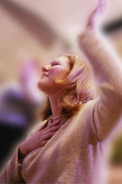 image of woman with arm raised worshiping God